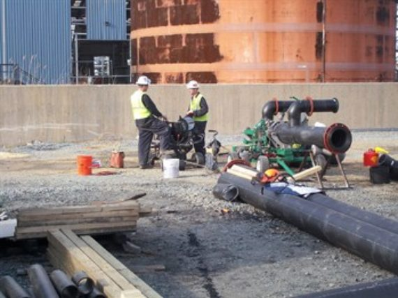 ISCO employees working on-site preparing piping for an industrial fusion project